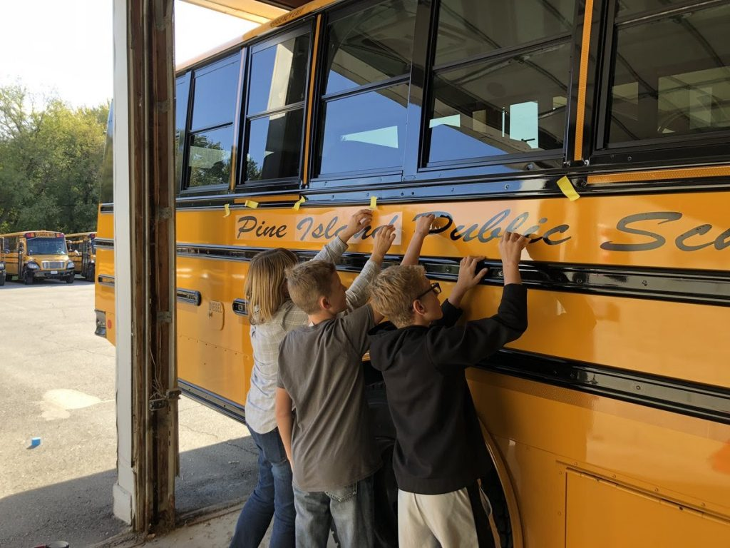 Middle school kids helping to put vinyl on the new bus